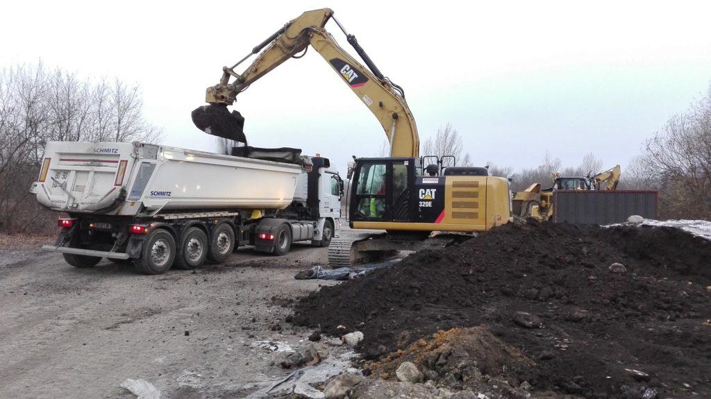 Pelleteuse chargeant un camion en terres dans le cadre d'une opération d'excavation des terres polluées